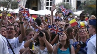 Wellwishers wave the Union Jack as the Duke and Duchess of Cambridge and Prince Harry appear in the main square at Mons