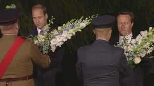The Duke of Cambridge and Prime Minister David Cameron accept the wreaths.