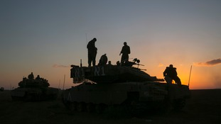 Israeli soldiers stand on a tank near the Israeli border with the Gaza Strip.