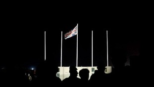 British service personnel stand in the darkness at Camp Bastion's vigil site .