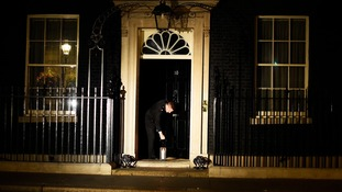 A police officer places the candle outside Downing Street.
