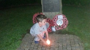 Michelle Adelle Hughes posted this picture possibly of her son with a candle at a soldier's graveside.