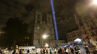 A view of Westminster Abbey, in London, as a column of white light - a light installation called 'spectra' by Japanese artist Ryoji Ikeda - is projected into the night sky, after a candle lit prayer vigil and solemn reflection to mark centenary of First World War