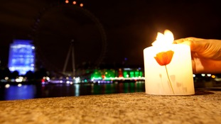 Hannah Mozley from London lights a candle as the London Eye on London's South Bank has its lights switched off as part of the national Lights Out campaign of remembrance, marking 100 years since Britain entered the First World War
