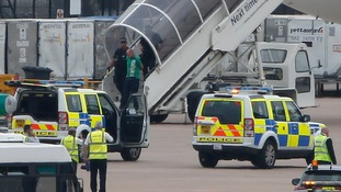 A white man is led off the plane by armed police.