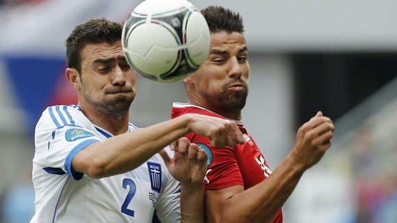 Greece&#x27;s Yiannis Maniatis, left, and Czech Republic&#x27;s Milan Baros fight for the ball in Wroclaw.