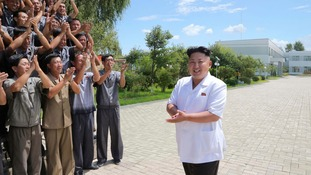 Workers clap North Korean leader Kim Jong Un.