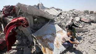 Palestinians sit next to ruins of their destroyed house in Khuzaa town.