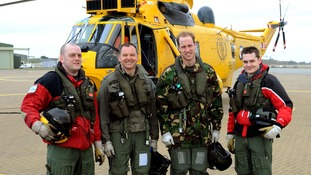 Prince William stands with his search and rescue crew, alongside their Sea King helicopter.