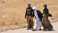 Displaced families from the minority Yazidi sect, fleeing the violence, walk on the outskirts of Sinjar.