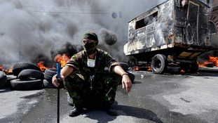 A protester sits in front of burning barricades during clashes with pro-government forces at Independence Square in Kiev August 7, 2014.