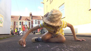 young girl writes on road with chalk