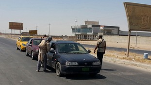 Islamic State militants man a checkpoint at a village in Nineveh province in Iraq today.