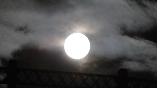 Full moon seen by the gas works on the Regents Canal in Hackney, London.