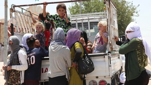 Displaced families from the minority Yazidi faith flee the violence in the Iraqi town of Sinjar.