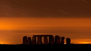 Stonehenge during the annual Perseid meteor shower in the night sky in Salisbury Plain.