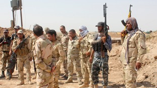 Iraqi security forces and volunteers take part in a mission to secure an area from Isil militants.