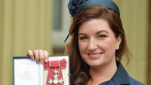 Karren Brady holding her CBE.