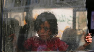 A girl looks through the window of a minibus as her family prepares to leave the Beit Hanoun neighbourhood in Gaza City.