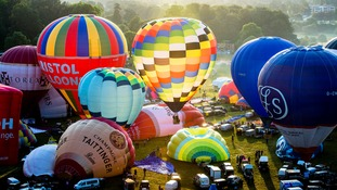 Hot air balloons are inflated at the 36th International Balloon Fiesta at the Ashton Court Estate near Bristol.