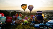Hot air balloons lift off during a mass ascent