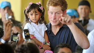 Prince Harry speaks to young children as he holds Mayara Pereira, 3, in his arms, during a visit to the Favella of Complexo do Alemao