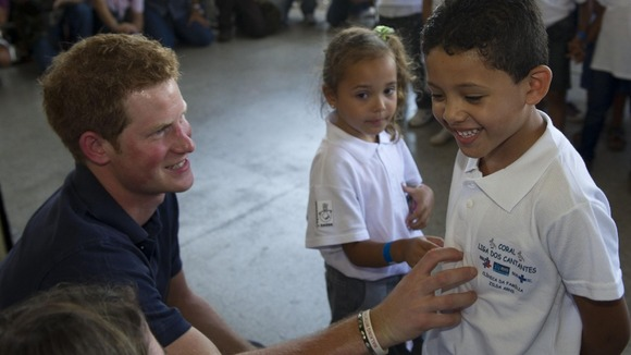 Prince Harry speaks to children during a visit to a health centre