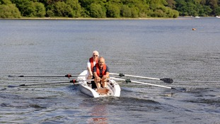Two rowers row in a double scull on Derwent Water