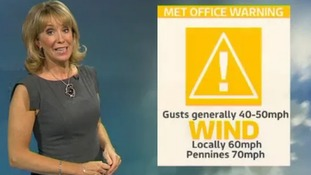 Emma in front of weather warning graphic