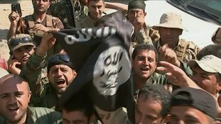 Islamic State fighters wave their flag