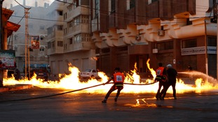 Firefighters try to extinguish a fire from a suspected air strike in Gaza City today.