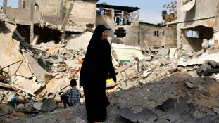 A Palestinian woman cries as she returns to her home said to have been destroyed by an Israeli air strike.