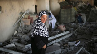 A Palestinian woman looks on as she returns to a badly-damaged residential building in Beit Lahiya.