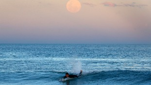 Surfer with super moon overhead