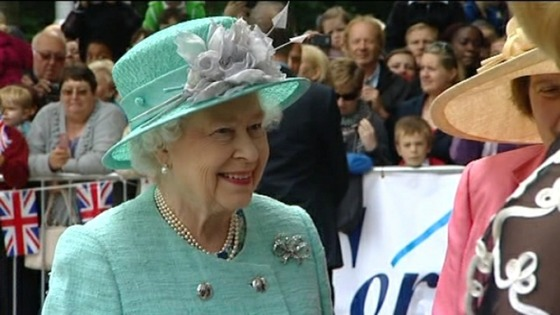 The Queen smiles at well-wishers as she arrives in Corby