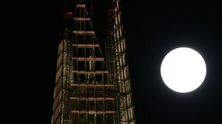 A view of the 'supermoon' rising behind The Shard building in London.