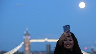 A woman takes a selfie as the supermoon rises over Tower Bridge in London.
