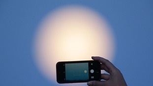 Ashleigh Richardson takes a picture on her mobile phone of the supermoon in south London.