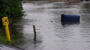 Bin floating along the flooded road.