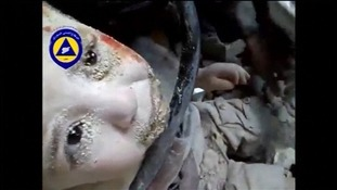 The young boy has rubble in his eyes as he is lifted from the wreckage.