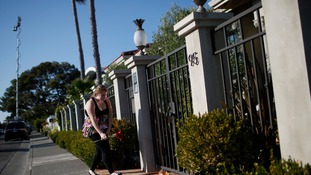 A woman leaves flowers outside the home of actor and comedian Robin Williams in Tiburon