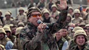 Comedian Robin Williams, wearing a camouflage jacket, entertains a cheering crowd of US Army troops at Baghdad airport