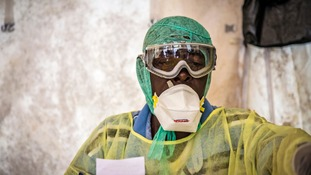 A health worker examines patients for Ebola inside a screening tent,