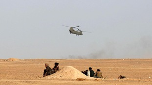Afghans watch as an RAF Chinook flies near Camp Bastion