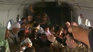 Iraqis huddle inside an Iraqi military helicopter after being rescued from Mount Sinjab