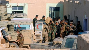 Kurdish peshmerga troops unload boxes of provisions at their base in the Iraqi's Dukra village