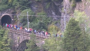 Passengers are seen walking on tracks in the Swiss Alps to reach safety.