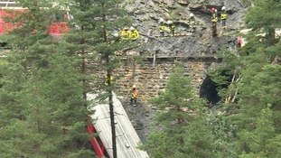 Rescuers try to get to one of the carriages which fell down a ravine.