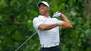 Tiger Woods of the U.S. grimaces after hitting his tee shot.