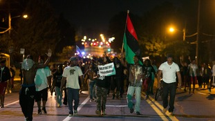Demonstrators march in the street while protesting the shooting death of black teenager Michael Brown in Ferguson, Missouri.
